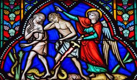 Stained glass window with image of an angel sending Adam and Eve from paradise.