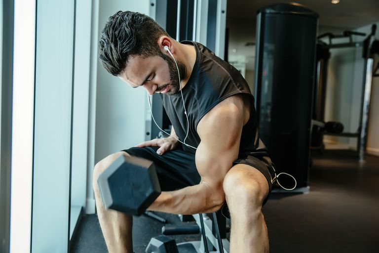 A muscular man curling a dumbbell at the gym
