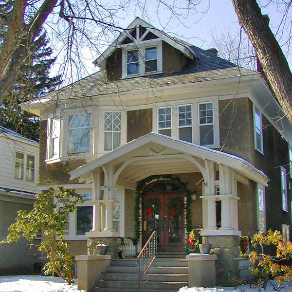 Sided in stucco, this Foursquare house has elaborate Craftsman stickwork around the porch.