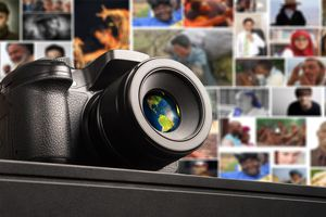 Digital camera on a table with a wall of pictures in the background.