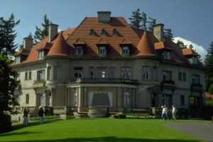 large stone mansion with red hipped roof, dormers, and turrets