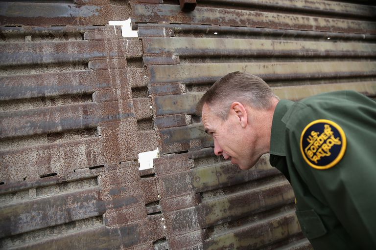U.S. Border Patrol agent Jerry Conlin peer through the U.S.-Mexico border fence