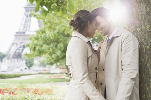 Couple kissing in park near Eiffel Tower, Paris, France