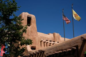 U.S flag and New Mexico state flag on an adobe building against a blue sky.