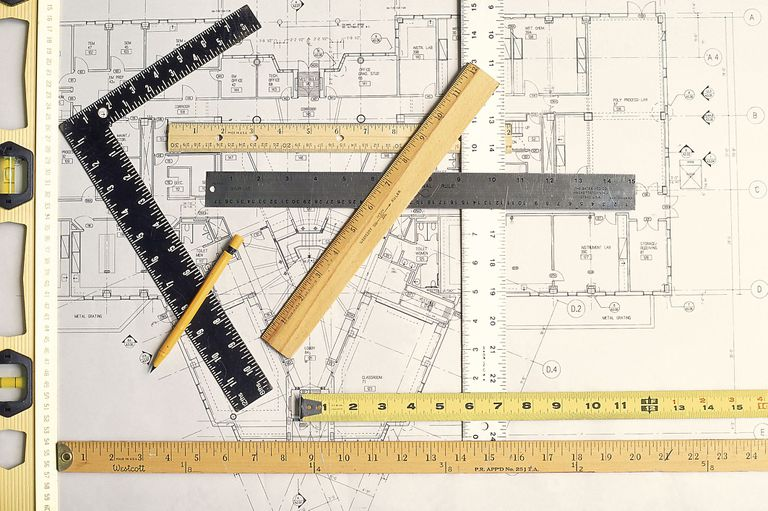 Blueprint with a variety of measuing sticks, tape measure, T-square and level