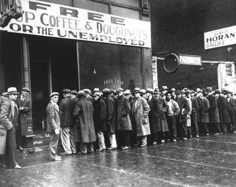 People standing on line for free food at a 1920s soup kitchen.