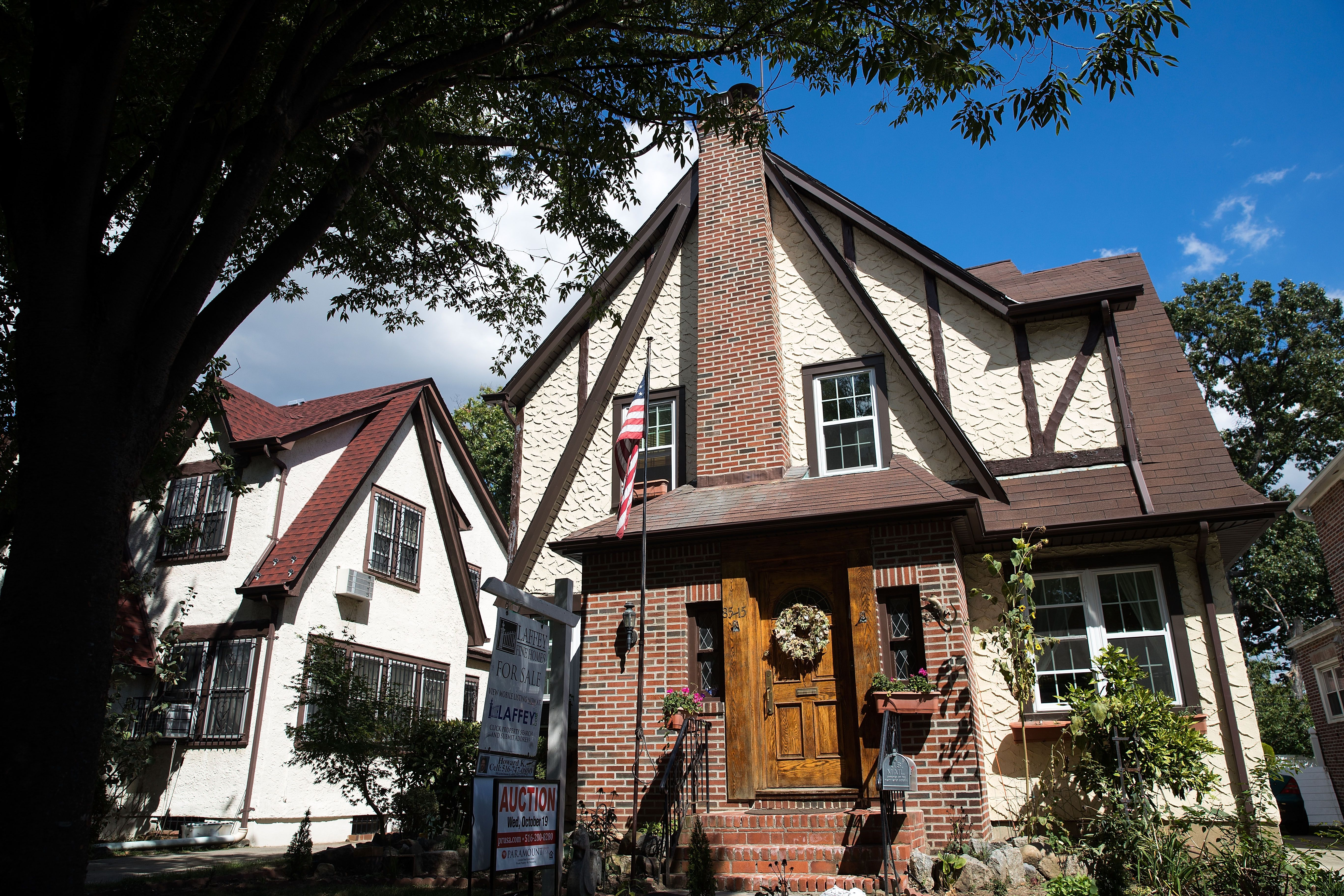 neighborhood home with Tudor details - half-timber work, pale yellow stucco, complicated roof lines, front chimney rising from a one-story brick front entryway