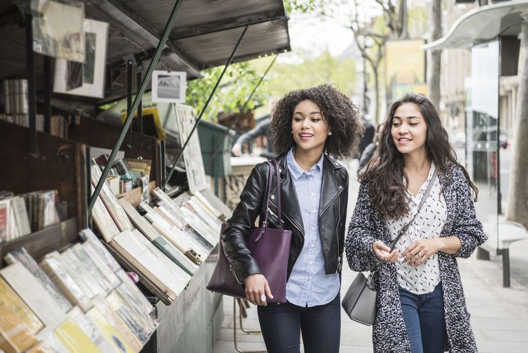 Two women walking past a bookshop