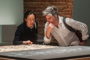 Female and male architects examine and discuss an exhibit
