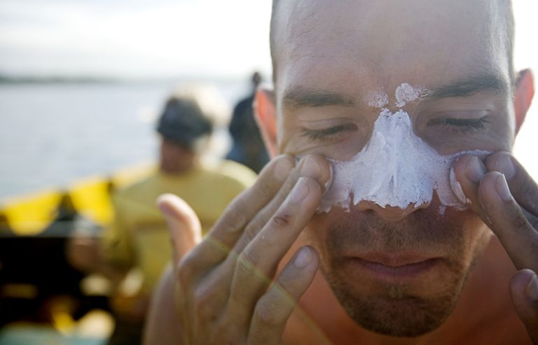 Man applies white zinc to his face and nose while sitting on a boat.