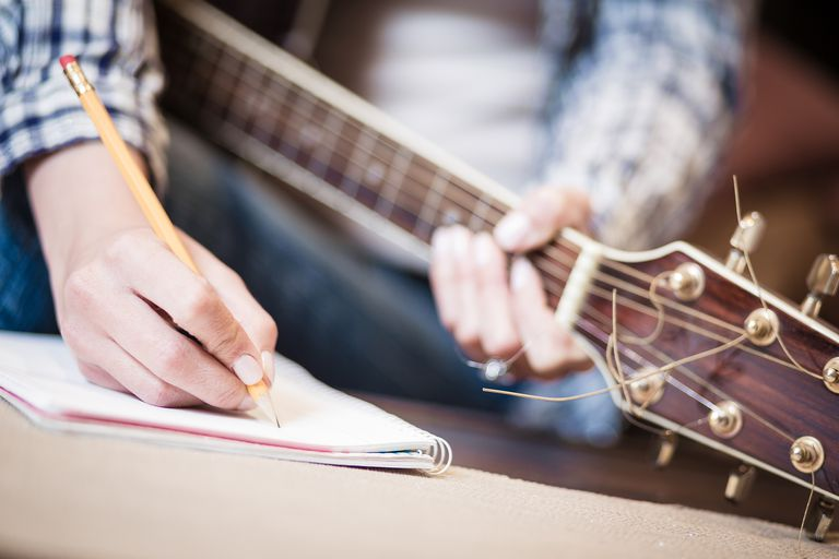Man holding guitar and writing musical composition