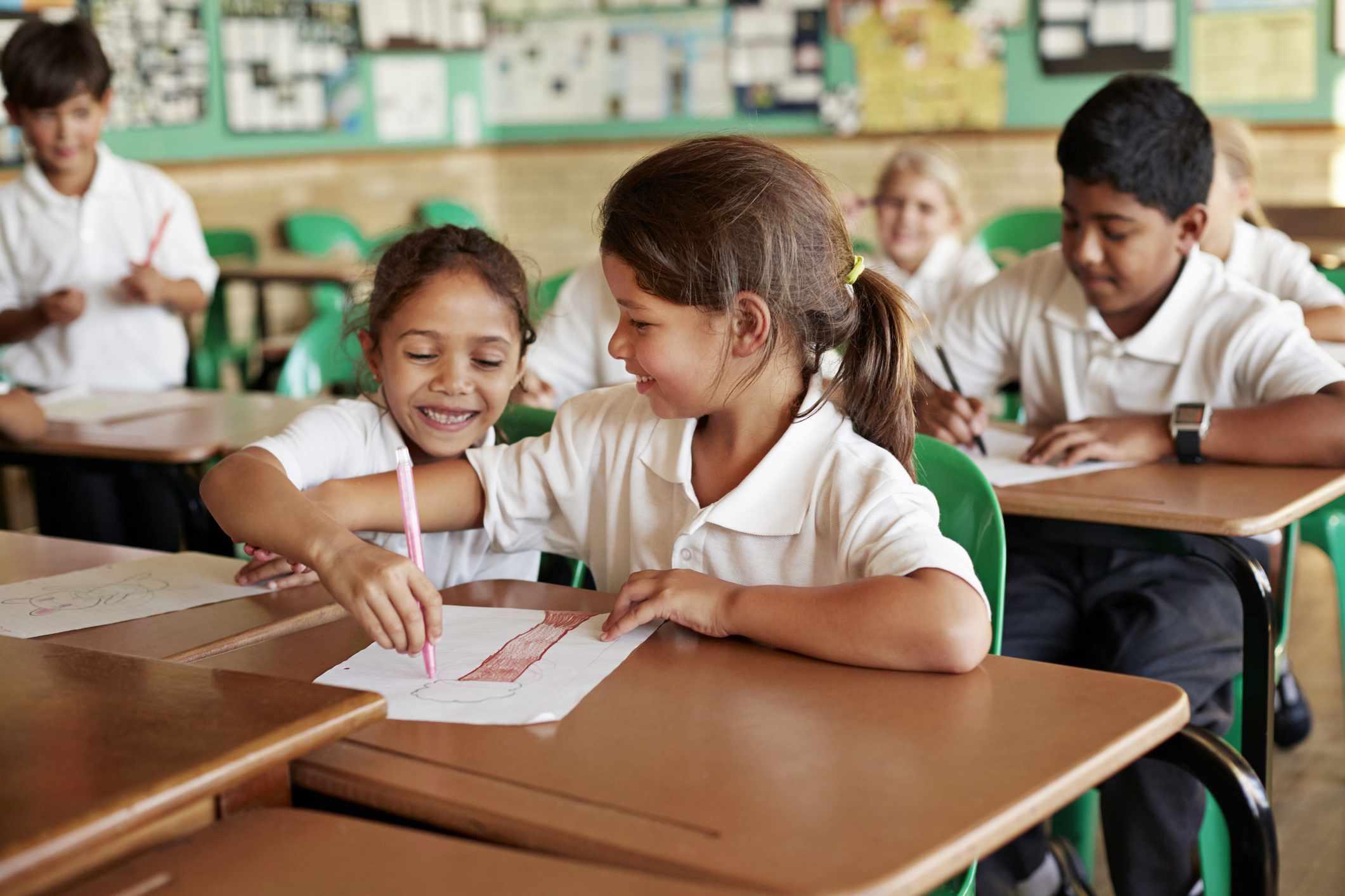 Schulmädchen, die auf Papier des anderen zeichnen