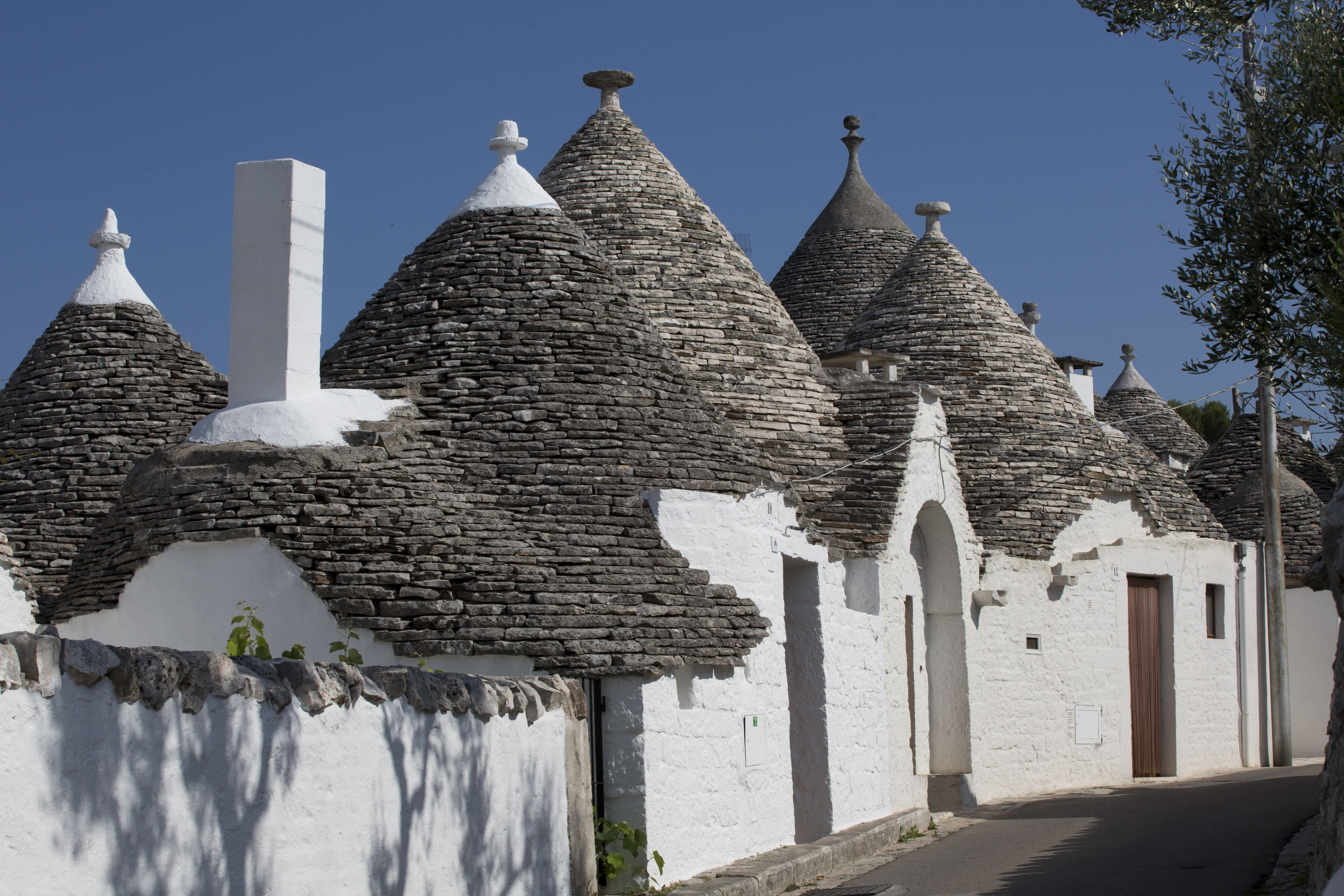 conical stone corbelled Trulli roofs on white houses along a narrow street
