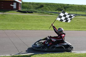 Go kart driver holding a checkered flag at the end of a race.