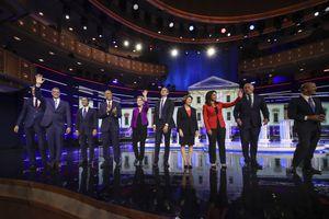 Several candidates waving onstage at a debate