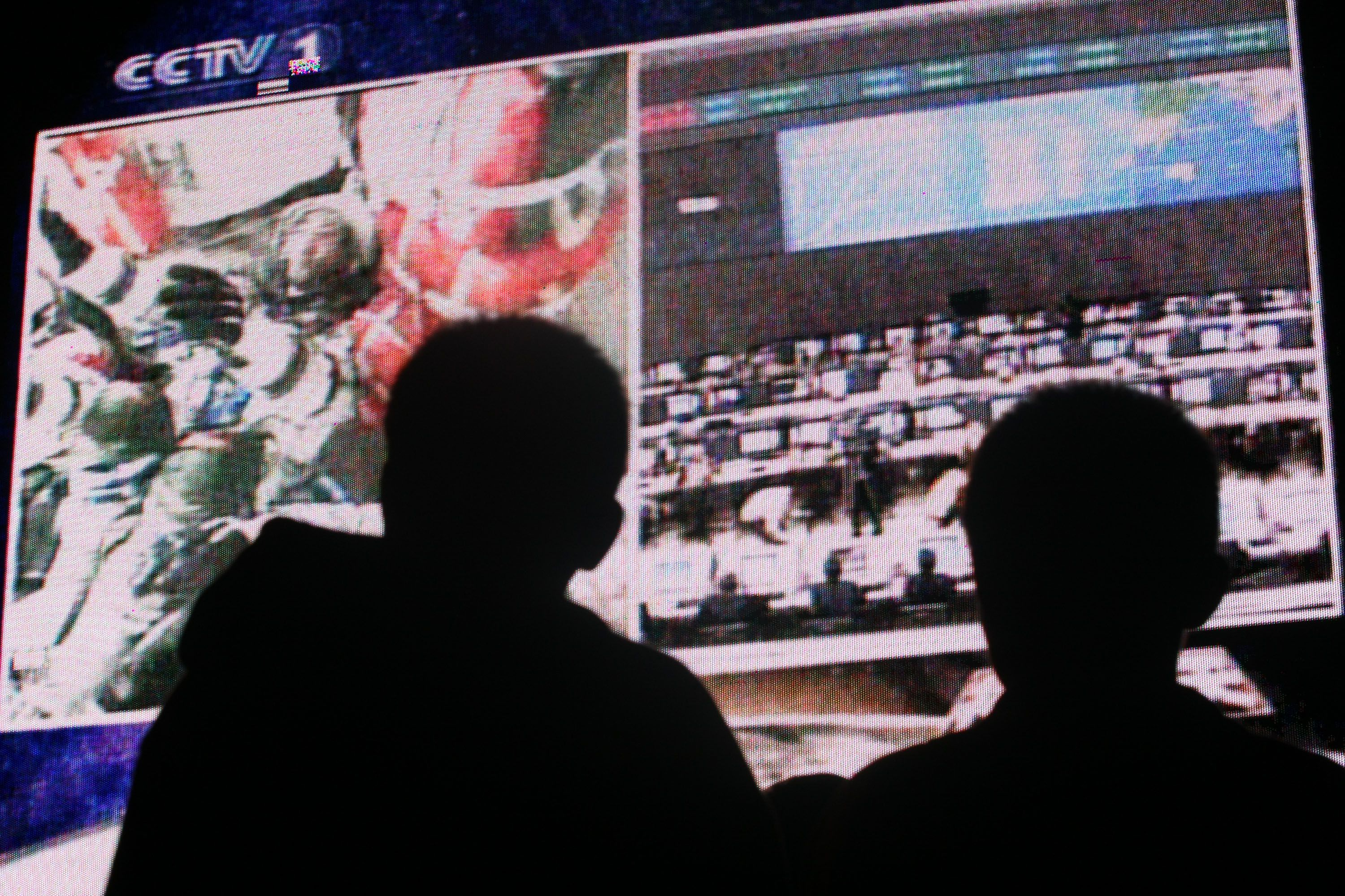 Two people watch a screen displaying the first-ever space walk by Chinese astronauts.