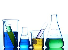 Beakers with different colored liquid against white background.