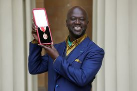 David Adjaye smiling at the camera and holding an award.