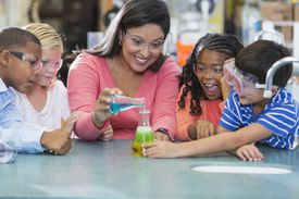 Multi-ethnic teacher and children in science lab