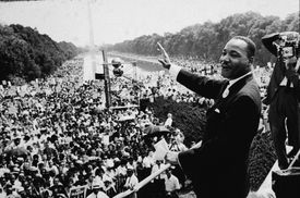 Martin Luther King, Jr. at the March On Washington waving to the crowd, black and white photograph.