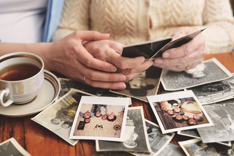 An elderly woman and a younger woman look at family photos