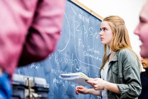 Students looking at a blackboard in math class.