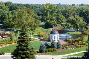 Pathways intersecting across a green campus, with a pond and rotunda in the center