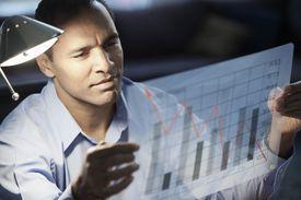 Businessman looking at bar graph chart