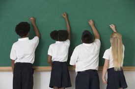 kids writing on chalkboard