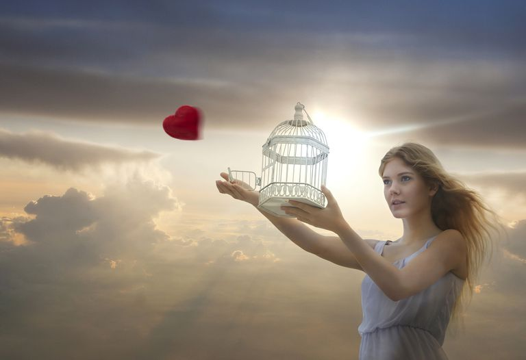 Caucasian woman releasing heart from birdcage
