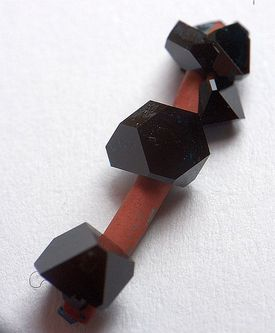 These are crystals of copper(II) acetate grown on a copper wire.