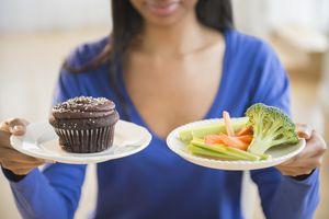 woman choosing vegetables or cupcake