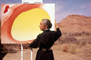 American artist Georgia O'Keeffe (1887 - 1986) stands at an easel outdoors, adjusting a canvas from her 'Pelvis Series- Red With Yellow,' Albuquerque, New Mexico, 1960