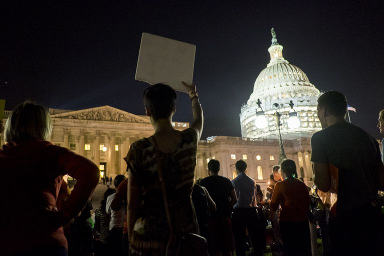 Night photo of protestors standing outside the US Capitol Building