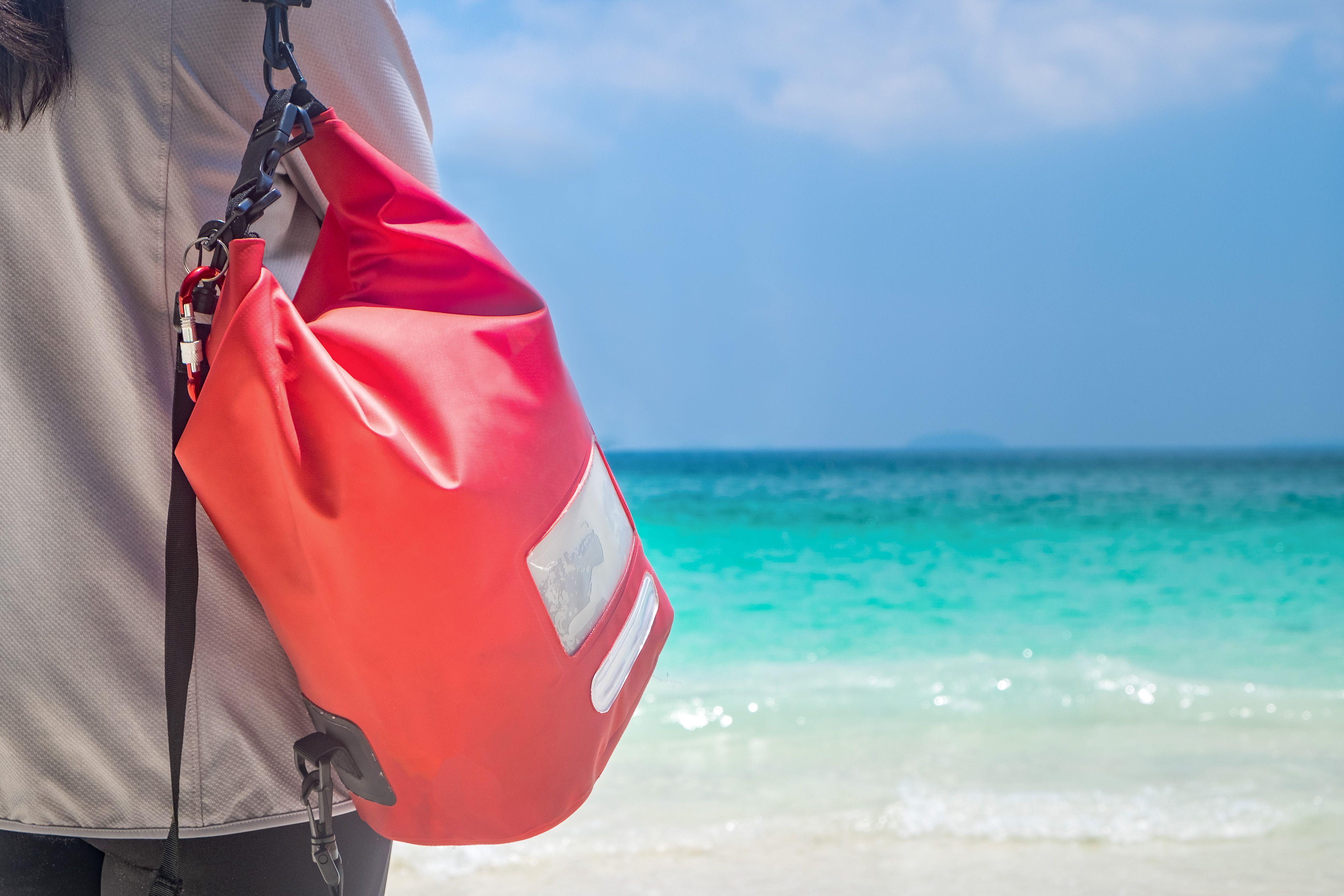 Woman Hang Dry Pack(Waterproof Luggage) on the Beach