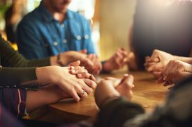 Group of people holding hands around table