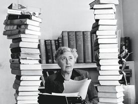 Black and white photo of Agatha Christie at her typewriter with her books in two tall stacks on either side.