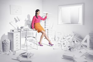 Woman with writer's block in an office with letters.