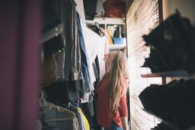 Woman looking at items in her closet.