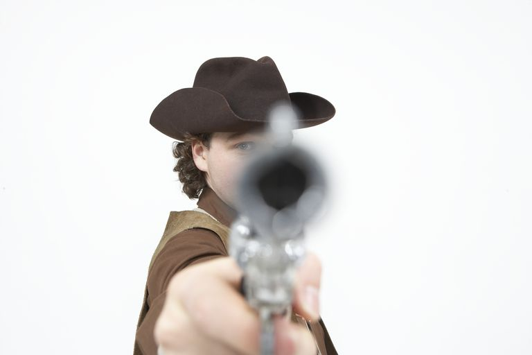 A cowboy pointing a pistol at the camera