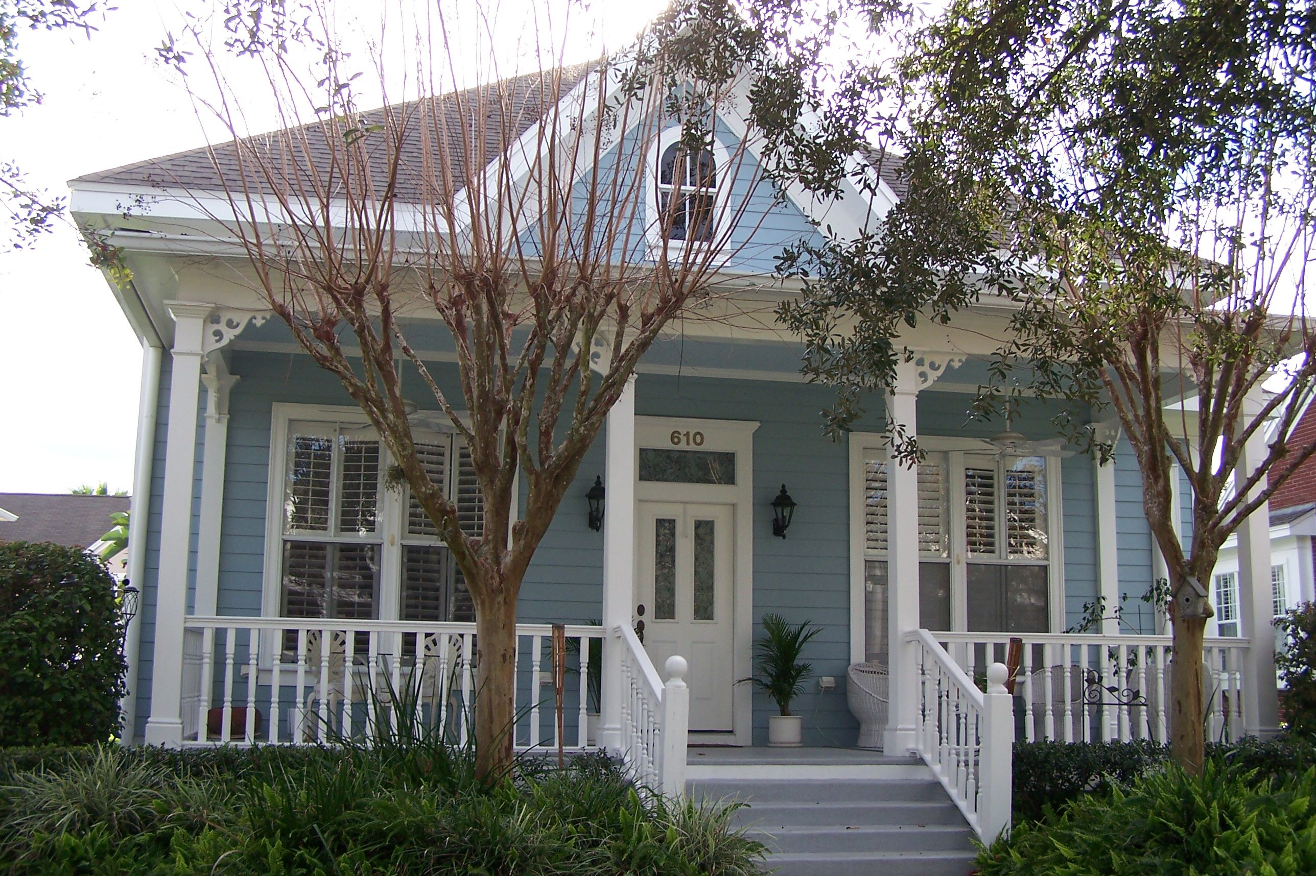 house with blue-siding and white trim, front porch with thin columns