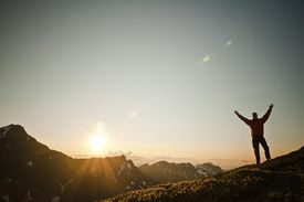 A man stands on a mountain peak at sunrise