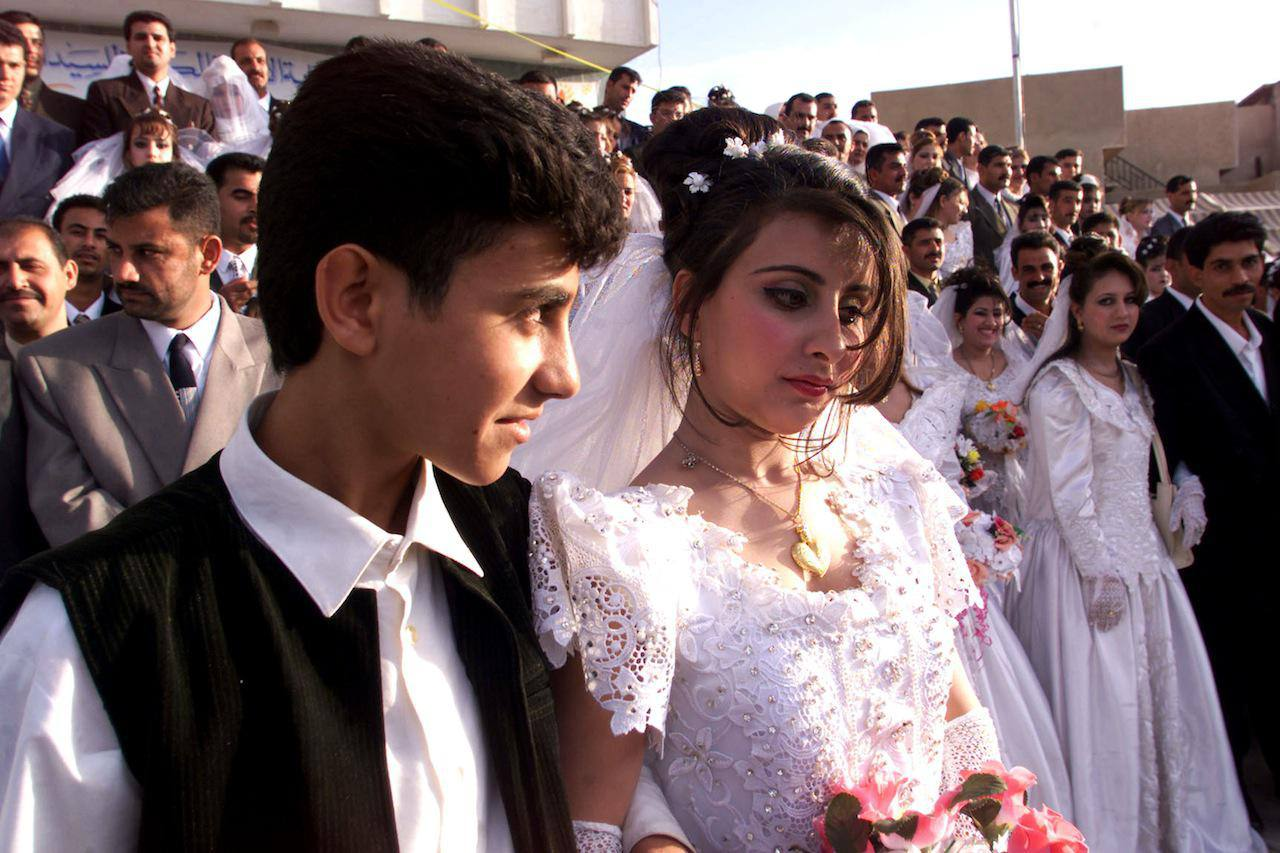 Omar, an 18-year-old groom, looks at his 15-year-old bride Khadija as other  newly married couples have photographs taken April 25, 2002 in Baghdad,  Iraq.
