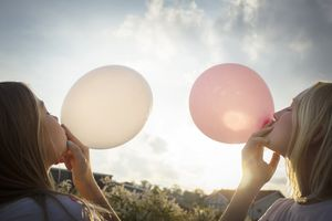 Girls blowing up balloons outdoors