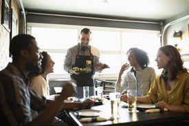 Waiter serving food to friends in restaurant