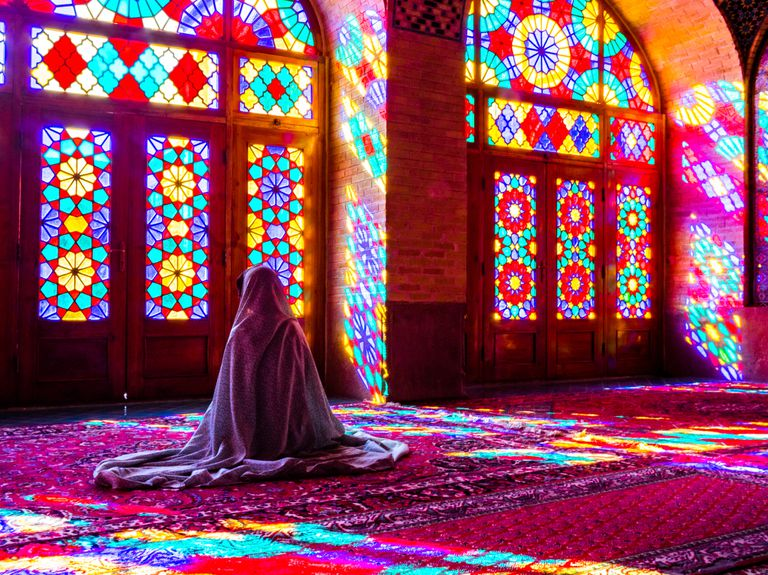 Worshipper in front of stained glass windows of Prayer Hall, Nasir-al Molk Mosque, Shiraz, Iran