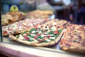 long flatbread pizzas at a counter