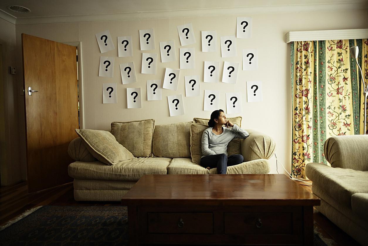 Mujer sentada en sofá con pared con símbolos de interrogación.