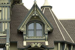 ornate gable dormer in green and cream colors, double arched windows, on steep roofed tower