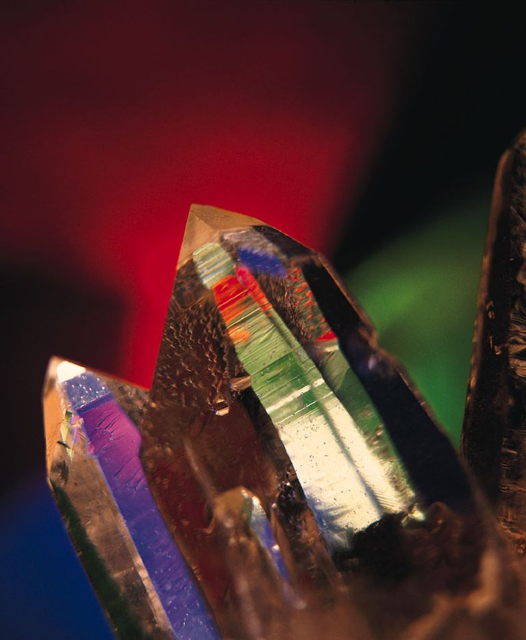 Multiple crystals against a colorful background.